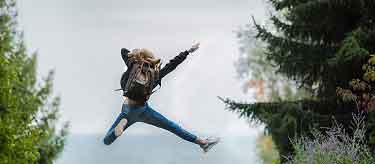 woman jumping with backpack
